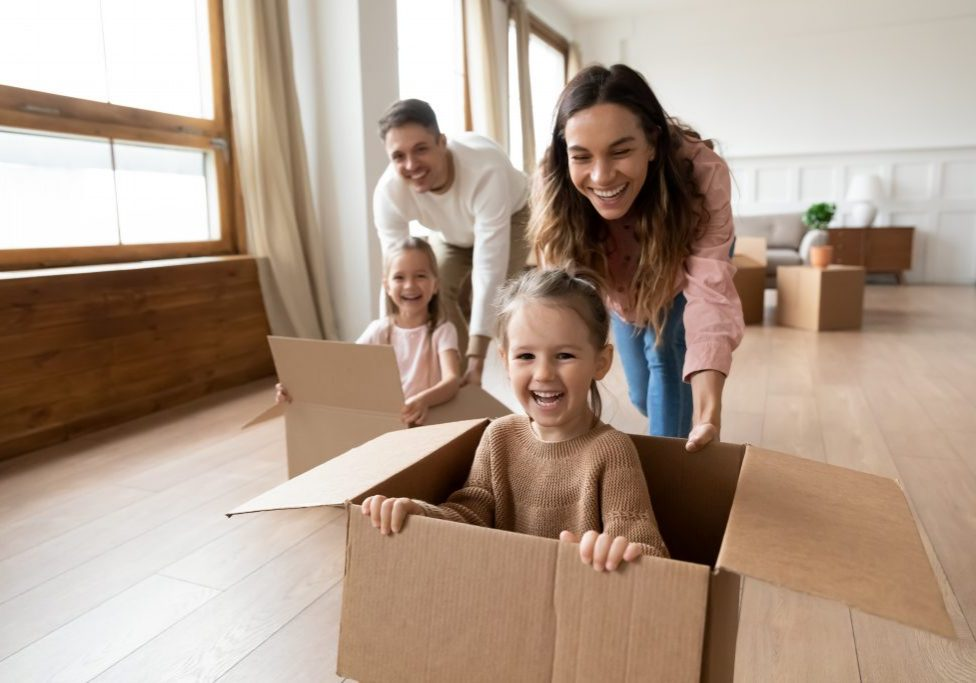 Happy parents playing with cute small kids daughters laughing on moving day, family tenants renters homeowners and children girls having fun riding in box in living room relocating new home concept